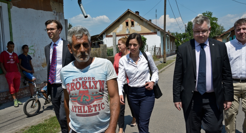 "Michael Georg Link, ODIHR Director, and Mirjam Karoly, Senior Adviser on Roma and Sinti Issues, are led through the ""Numbered Streets"" neighbourhood by local Roma activists during the field assessment visit to Miskolc, Hungary, on 1 July 2015. Copyright OSCE-ODIHR."